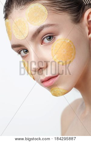 Beautiful young cheerful woman with refreshing mask on her face isolated on white background, closeup