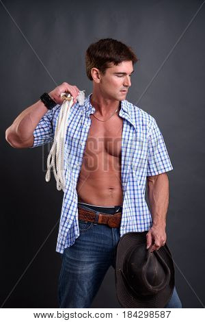 The handsome man is holding a lasso.