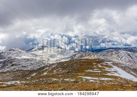 Snow Covered Peaks And Yellow Grass Under Clouds. Australian Alps Landscape