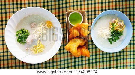 flat lay two bowls of porridge and deep fried dough sticks on table for breakfast