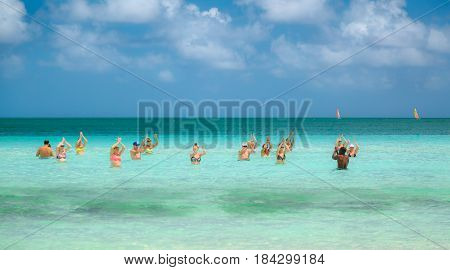 Cayo Coco island, Playo Coco beach, Cuba, Aug.31, 2015, gorgeous beautiful inviting view of group of people enjoying their time by doing dancing water sport exercises in tranquil turquoise ocean on sunny day