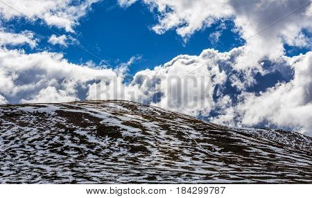 Panorama Of Snow Patches On Mountains And Fluffy Clouds On Bright Sunny Day