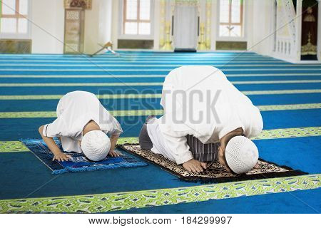 Picture of a devout family posing prostration while praying to the Allah in the mosque