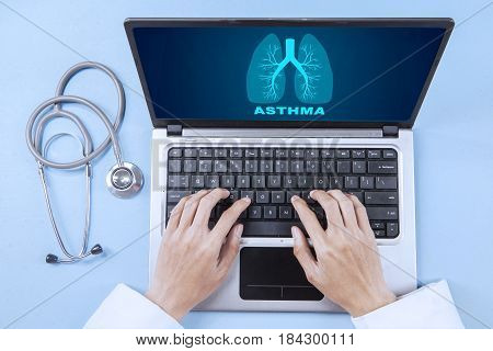 High angle view of male doctor's hand typing on the laptop keyboard with lungs symbol and asthma word on the screen