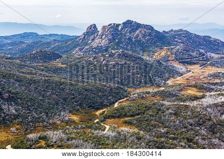 Winding Dirt Road And Rugged Cliffs At Mount Buffalo National Park, Victoria, Australia. Vertical Im