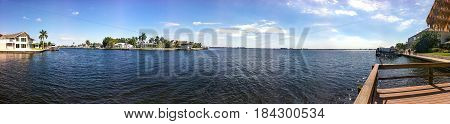 A wide river with houses and blue sky in Cape Coral Florida
