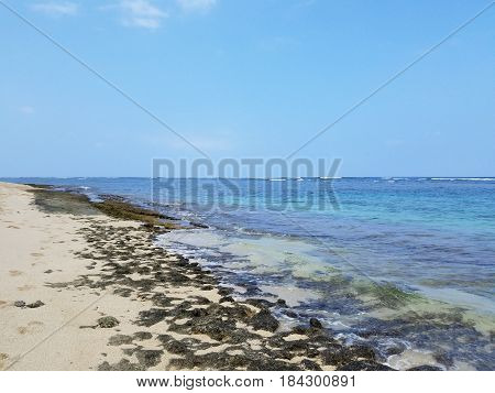 Rocky beach with Shallow wavy ocean waters of Camp Mokuleia Beach looking into the pacific ocean with a clear blue sky on Oahu.