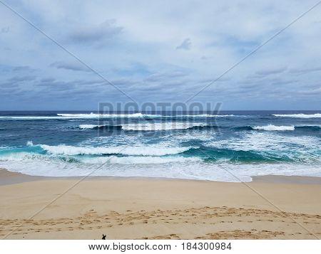Waves break and crash towards the Hanakailio Beach on the North Shore of Oahu Hawaii.