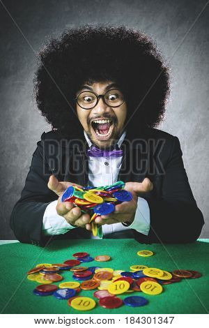 Portrait of lucky gambler with Afro hair winning a gambling and holding many chip on his hands with happy expression
