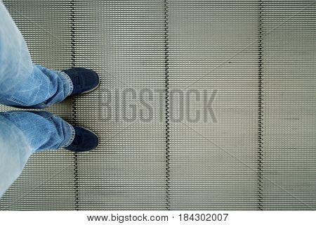High angle of a man's foot wearing a sneaker while standing on the escalator