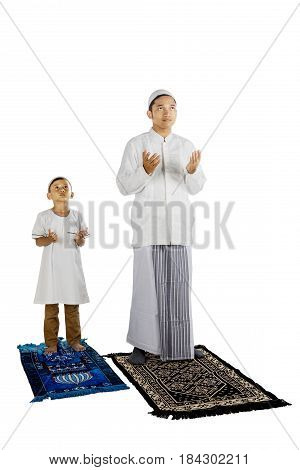 Image of a Muslim father with his son praying to the Allah while standing in the studio