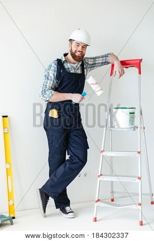 Full-length shot of smiling bearded builder with roll and paint near ladder isolated
