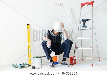 Young tired builder sleeping near repair equipment isolated