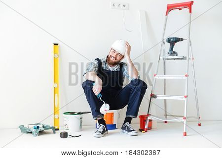 Happy bearded builder sitting on bucket near tools and looking camera isolated