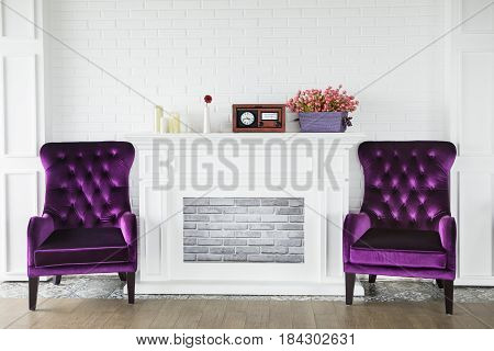 Image of two purple armchairs near a fireplace with candles radio player and flowers in the old fashion living room