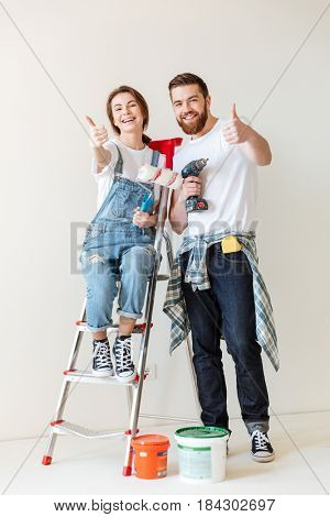 Happy lovers showing thumbs up while making repair in new house isolated