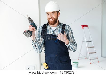 Young handsome builder man touching himself and looking camera isolated