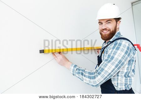 Young positive man holding ruler and looking camera isolated