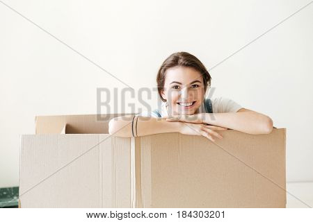 Happy young woman peeking out from box isolated over white