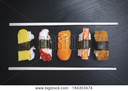 Top view of delicious nigiri sushi with chopsticks on the wooden table