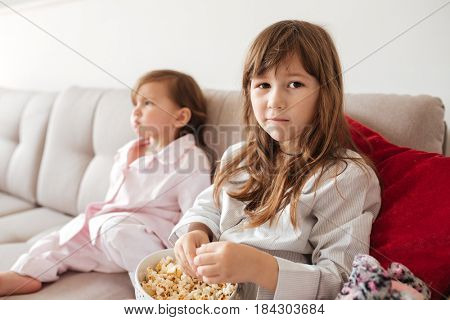 Portrait of little girl with popcorn sitting on couch near younger sister