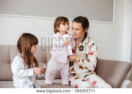 Mother sitting near her little pensive children with postcards