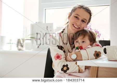 Beautiful young mother hugging her little child with nipple