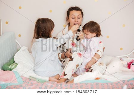 Little daughters feed her mother while they sitting on bed