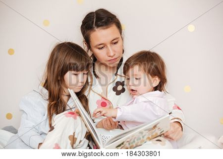 Young woman with daughters reading book attentively