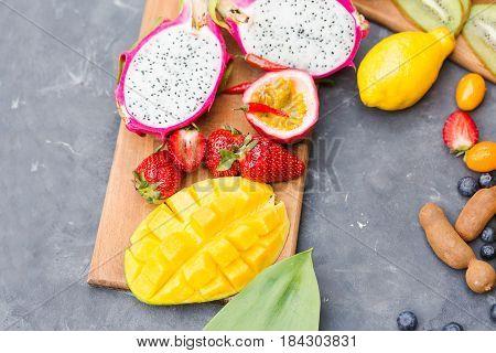 Exotic fruits. Summer photo concept. Mango. Papaya. A pineapple. Avocado. Kiwi. Pitahaya. Kumhvat. Copyspase. Fresh fruits. Exotic fruits on a gray background. Blueberry. Strawberry. Physalis. Tamarind. Lemon.