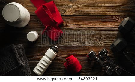 Grey Towel Protein Shake Bottle Dumbbell Plate White Jar With Whey Protein Red Hand Wrap Sneakers On