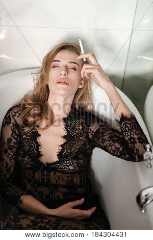 Pretty young woman smoking in bath