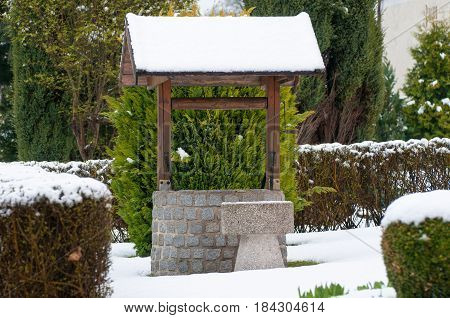 Retro wooden well water in the snow