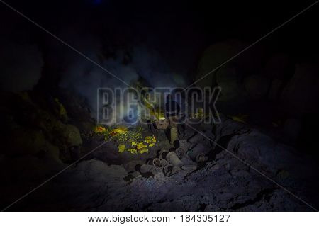 KAWEH IJEN, INDONESIA: Man wearing headlight working in sulfur mine, extracting yellow mineral rocks in dark environment.
