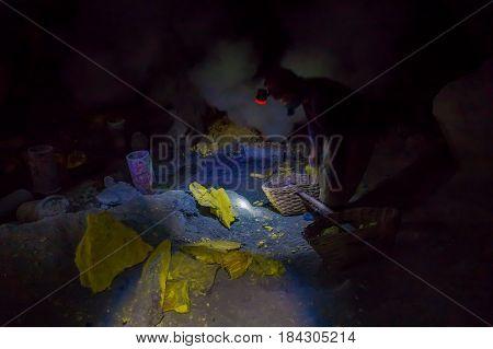 KAWEH IJEN, INDONESIA: Man wearing headlight working in sulfur mine, extracting yellow mineral rocks in dark environment.