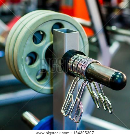 Barbell clamps on weight bar in fitness center