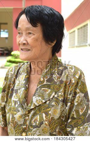 An elderly asian woman smiling outdoor facing sideway