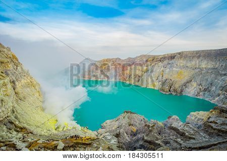 KAWEH IJEN, INDONESIA: Spectacular overview of volcanic crater lake with beautiful blue sky, tourists visible in the distance.