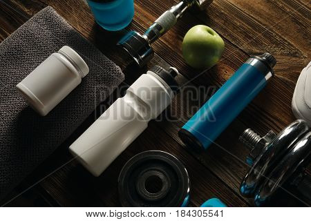 Grey Towel Protein Shake Bottle Dumbbell Plate White Jar With Whey Protein Sneakers On Wooden Floor