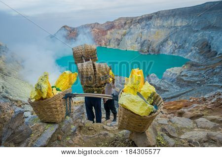 KAWEH IJEN, INDONESIA: Local miners carrying heavy baskets of yellow sulfur rocks up mountain side, tourist hiking attraction located inside volcanic crater, spectacular nature.