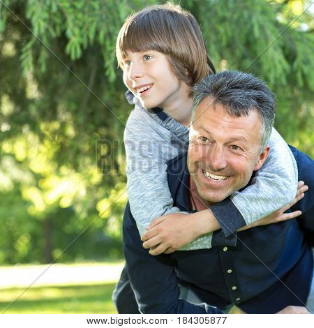 Portrait of father with his son having fun in summer park. Piggyback. Family fun. Happy boy playing with dad summer nature outdoor