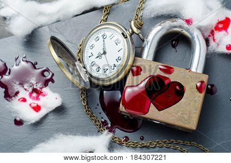 Red heart shape over padlock with vintage pocket watch and blood on black stone background