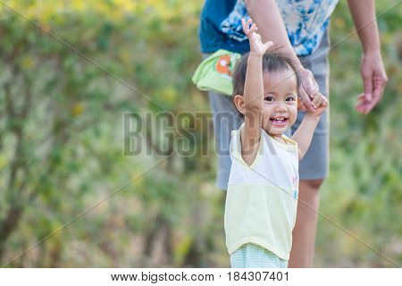 Asian baby girl learning to walk with her mother in the park.
