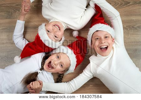 three kids in Santa hats lying on wooden background, having fun and happy emotions, winter holiday concept