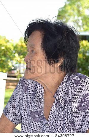 A sad looking asian woman looking sideway outdoor
