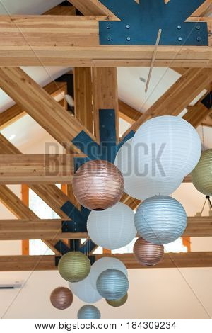 Wedding reception decor of white, gold, and silver paper lanterns hung high in the rafters at a wedding venue.
