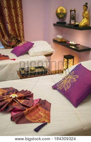 Lounges for thai massage with towels, pillows and flowers in empty room