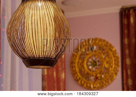 Stylish lamp hangs from ceiling in room with asian decoration, shallow dof