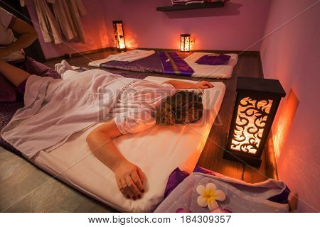 Young woman getting thai massage on mat in purple spa room with lanterns on floor