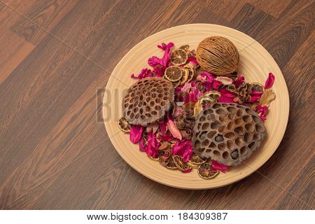 Dried fruits, citrus, petals of flowers are on plate on wooden floor